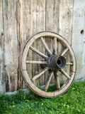 Old wooden wagon wheel. Resting against rustic wooden fence Stock Image