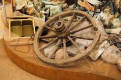 Old wooden wagon wheel rests on the rocks. Bowler for food Royalty Free Stock Photography