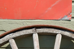 Old wooden Wagon Wheel. An old wooden wagon wheel sits up against an old wall Stock Photography