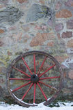 Old wooden wagon wheel. On a stone wall in winter Royalty Free Stock Photos
