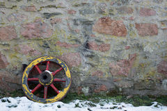 Old wooden wagon wheel. On a stone wall in winter Stock Images