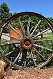 Old wooden wagon wheels on a cart holding flower pots royalty free stock image