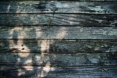 Old wooden wall from boards with peeling paint and sun glare. Texture of an old wooden wall from boards with peeling paint and sun glare Royalty Free Stock Images