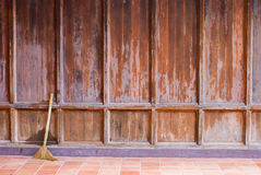 Old wooden wall with a broom ready for cleaning work Stock Photos
