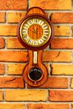 Old wooden wall clock with barometer and thermometer on the bric royalty free stock photography