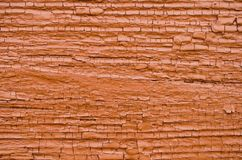 Old wooden wall with cracked dark orange paint stock photo