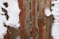 Old wooden wall. Old wooden door with a handle in the snow, background Royalty Free Stock Image