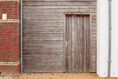 Old wooden wall with a door between the two houses Royalty Free Stock Images