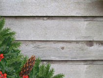 Old wooden wall with holly and pine cones festive holiday background Stock Photos
