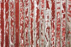 Old wooden wall painted with dark red color peeling revealed rustic texture. The old wooden wall painted with dark red color cracking, peeling and revealed the Stock Images