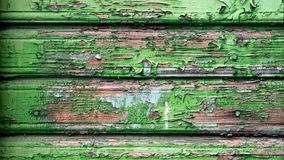 Old wooden wall peeling green paint. Close-up of an old wooden wall with peeling green paint. Close-up of a green wooden floor from the lining, wooden background Stock Photos