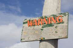 Old Wooden Warning Sign. With blue sky and clouds background Royalty Free Stock Photo
