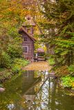 Old wooden water mill in the forest with reflect on water at autumn royalty free stock image