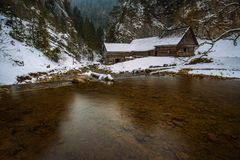 Old wooden water mill in winter. Old wooden water mill at National Nature Reserve Kvacianska dolina in Slovakia in winter.  It has been restored and serves as a Royalty Free Stock Image