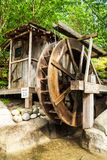 Old wooden water mill with the wheel turning Stock Image