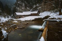 Old wooden water mill in winter. Old wooden water mill at National Nature Reserve Kvacianska dolina in Slovakia in winter.  It has been restored and serves as a Royalty Free Stock Photo