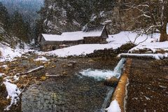 Old wooden water mill in winter with snow falling Royalty Free Stock Images