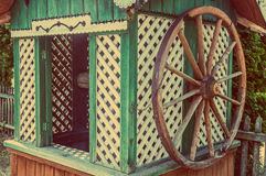 Old wooden water well house with a large wheel Stock Image