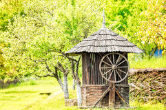 Old Wooden Water Well House. With a large wheel near a woven willow fence with green trees in the background Stock Photography