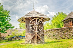 Old Wooden Water Well House. With a large wheel near a woven willow fence with green trees in the background Stock Photos