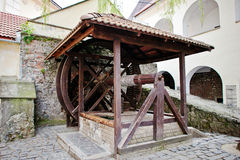 Old wooden water well with pulley and bucket. Palanok castle.  Royalty Free Stock Photography