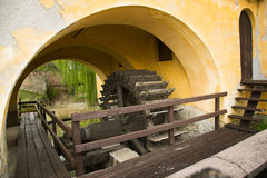 Old Wooden Watermill Under Yellow Painted Arches Of Ancient Building Royalty Free Stock Photos