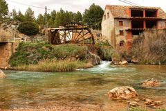 Old wooden waterwheel and Cabriel River on its way through Casas del Rio village, Albacete, Spain. Landscape between cane field and mountains Stock Photography