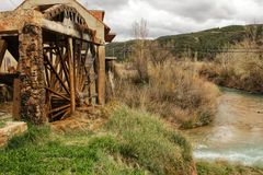 Old wooden waterwheel and Cabriel River on its way through Casas del Rio village, Albacete, Spain. Landscape between cane field and mountains Stock Photo
