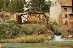 Old wooden waterwheel and Cabriel River on its way through Casas del Rio village, Albacete, Spain. Landscape between cane field and mountains Royalty Free Stock Photos