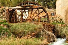 Old wooden waterwheel and Cabriel River on its way through Casas del Rio village, Albacete, Spain. Landscape between cane field and mountains Stock Photos