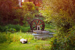 Old wooden waterwheel watermill on a horse farm. The old water wheel covered with moss. Flowing water to the mill. Old technology. Energy water movement Royalty Free Stock Photos