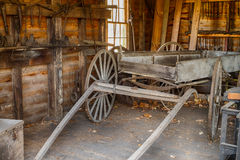 An old wooden and weathered wagon waiting to be restored in an o Royalty Free Stock Image