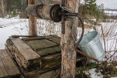 Old wooden well. The old wooden well on the edge of the village with a metal bucket for water lifting royalty free stock photo