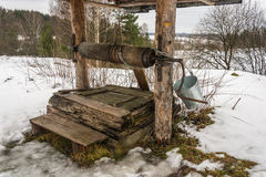 Old wooden well. The old wooden well on the edge of the village with a metal bucket for water lifting stock photography