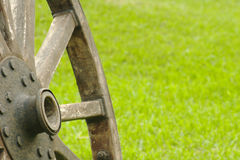 Old Wooden Wheel. Standing with grass background (Selective Focus Stock Image