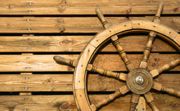 Old wooden wheel. On a wooden wall Stock Photos