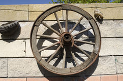 Old wooden wheel hanging on the stone wall in the garden Royalty Free Stock Photo