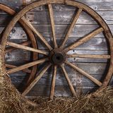 Old wooden wheel on a hay Royalty Free Stock Images