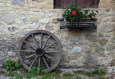 An old wooden wheel leaning against a stone wall Stock Photo