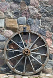 Old wooden wheel is placed near wall Royalty Free Stock Images
