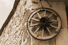 Old wooden wheel on a wall of. An old wooden wheel on a wall of abandoned house Royalty Free Stock Image