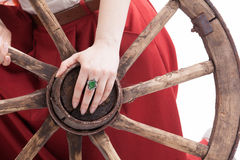 Old wooden wheel an woman's hand with a ring Stock Photo