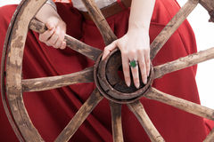 Old wooden wheel an woman's hands with a ring Stock Images