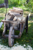 Old wooden wheelbarrow loaded with firewood. An antique wooden wheelbarrow for transportation of firewood Royalty Free Stock Image