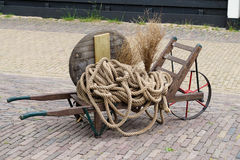 Old wooden wheelbarrow loaded with rope Stock Photo