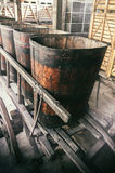 Old wooden wheelbarrow with vats Stock Photo