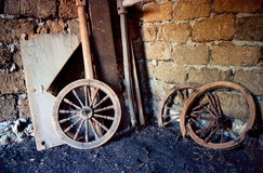 Old wooden wheels, broken and abandoned. They lie in a stable, dirty and dusty Stock Photos