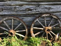 Old wooden wheels from a cart on the background of an old wooden shed stock photography