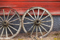 Old wooden wheels stand above red wall Royalty Free Stock Images