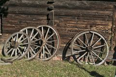 Old wooden wheels for wagon with metal rings near a wooden hut stock photography